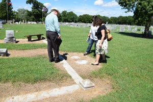 Randy Lucas, Stacey Graham, and Lydia Simpson examine a gravestone on the ground.